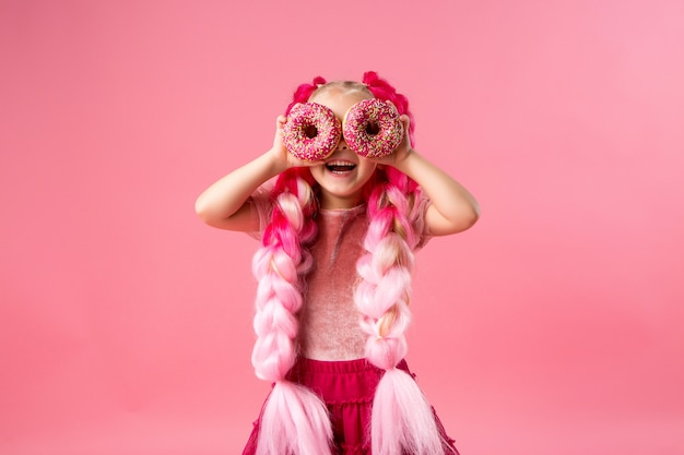 Petite fille avec des tresses kanekalon avec des beignets sur fond rose