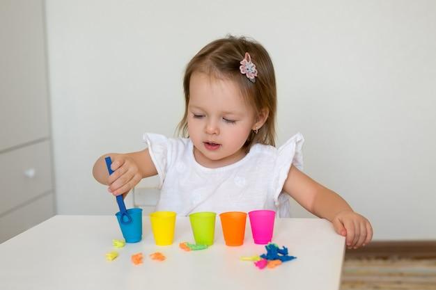 Une petite fille trie les figures d'animaux par couleur et les jette dans la tasse appropriée.