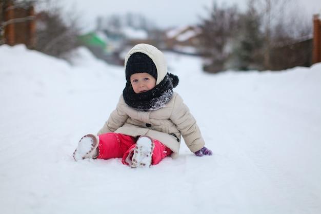 Petite fille triste assis sur la neige au jour d'hiver ensoleillé
