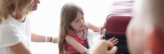 Une petite fille triste et bouleversée fait sa valise avec les parents en gros plan