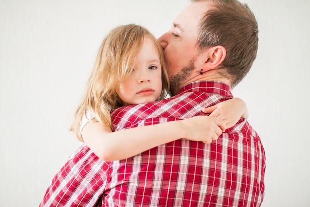 Petite fille triste sur les bras de papa. la fille embrasse papa.