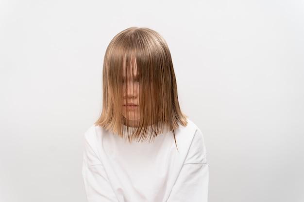 La petite fille triste avec des cheveux couvre le visage sur le blanc
