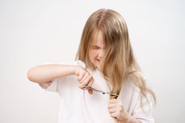 La petite fille triste cisaille les cheveux longs avec des ciseaux sur fond blanc. coupe de cheveux à la mode pour le bébé. coiffeur. les farces des enfants. la coupe de cheveux