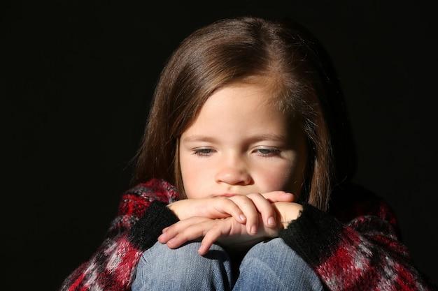 Petite fille triste sur fond noir, gros plan