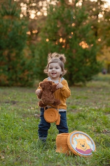 Petite fille triste mignonne tenant dans les mains un ours en peluche brun, un enfant contrarié qui passe du temps à l'extérieur au printemps