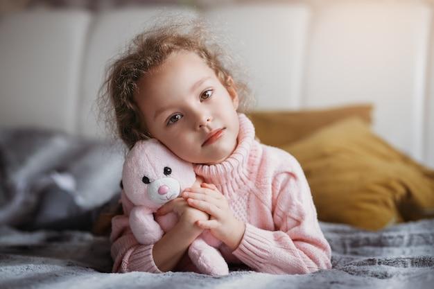 Petite fille triste avec une peluche sur le lit