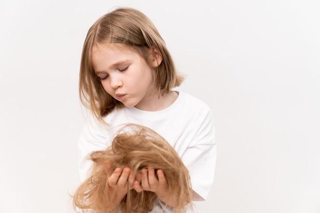 Une petite fille triste tient dans les mains les cheveux coupés après avoir coupé sur un fond blanc. signifie prendre soin des cheveux des enfants. salon de beauté pour enfants.