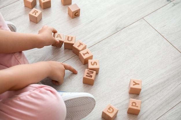 Petite fille avec trouble autistique jouant avec des cubes sur marbre