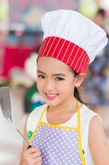 Petite fille en uniforme de chef avec une louche