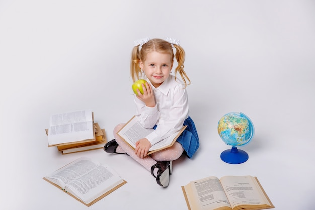 Petite fille en uniforme d'école sur fond blanc, lisant un livre