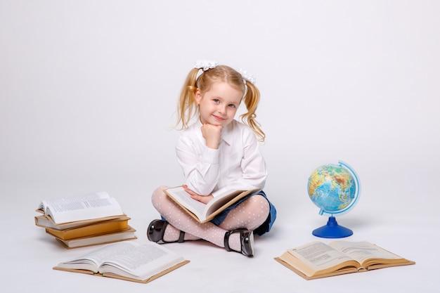 Petite fille en uniforme scolaire assis sur blanc