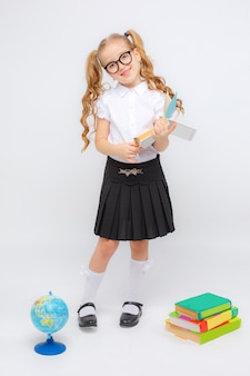 Une petite fille en uniforme scolaire et lunettes tient un globe dans ses mains sur un espace blanc