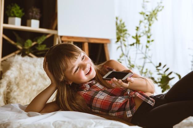 Petite fille utilisant différents gadgets à la maison