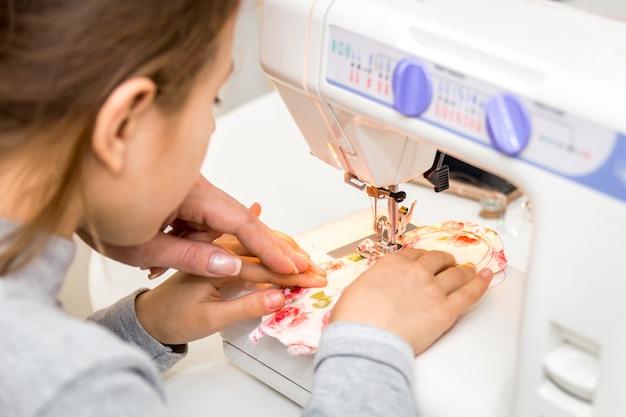 Petite fille utilisant une machine à coudre pour faire de l'artisanat