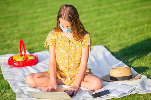 Petite fille utilisant un ordinateur portable pour étudier à l'extérieur dans le parc