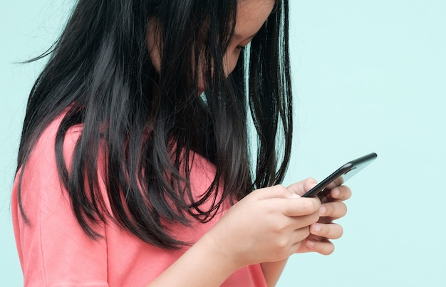 Petite fille utilisant un smartphone en studio