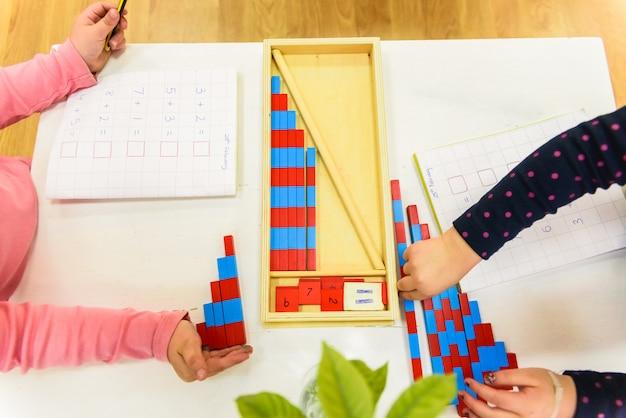 Petite fille utilisant des tiges de bois peintes pour apprendre à s'ajouter à une école.