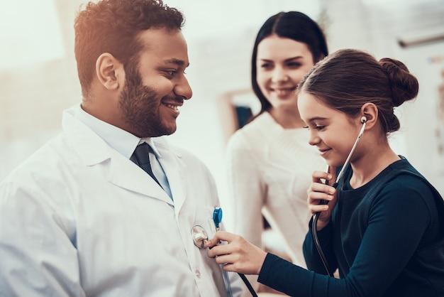 Petite fille utilise un stéthoscope chez le médecin.