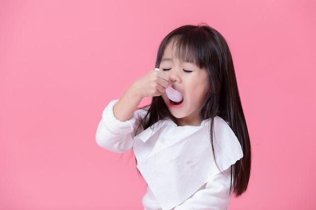 Petite fille va manger de la nourriture avec une cuillère en plastique avec un mouchoir en tablier en mur rose.