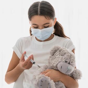 Petite fille vaccinant son jouet
