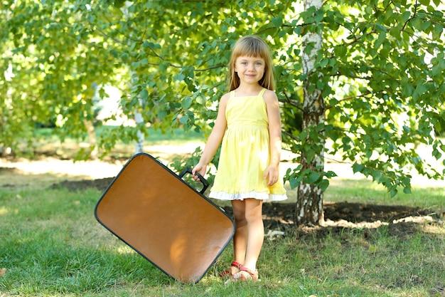 Petite fille avec valise sur l'herbe dans le parc