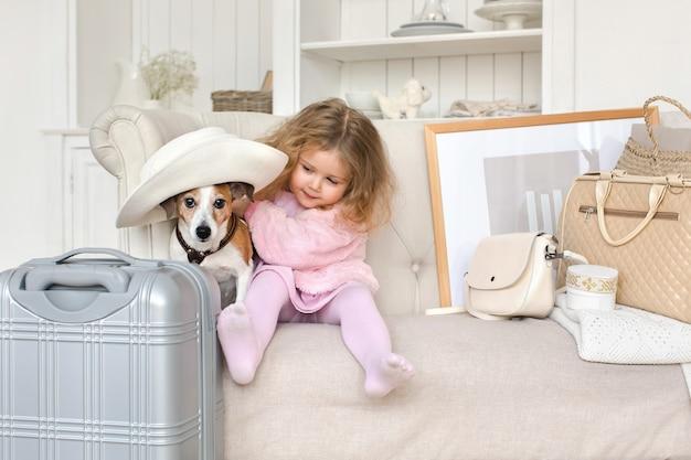 Une petite fille avec valises et un chien en intérieur