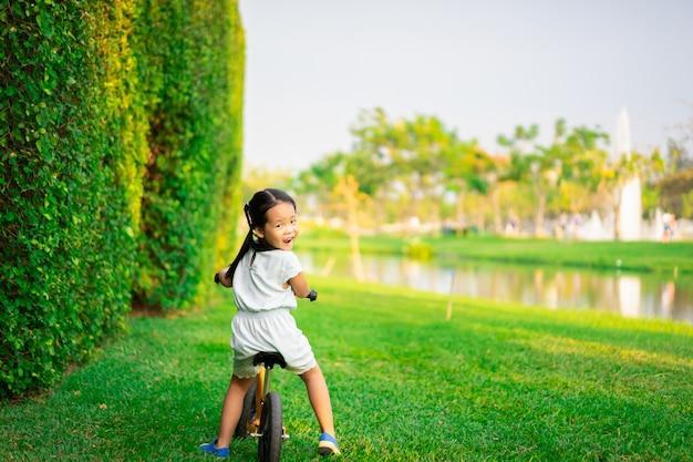 Petite fille à vélo d'équilibre dans le parc