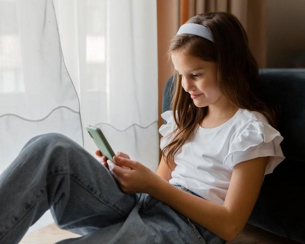 Petite fille vérifiant son téléphone