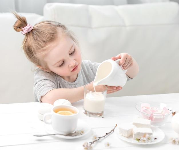 Petite fille, verser le lait dans sa tasse de thé