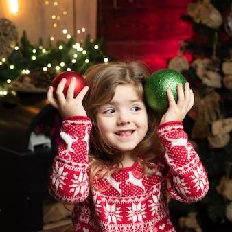 Petite fille en veste rouge avec des flocons de neige et des cerfs concept de vacances heureuse petite fille d'âge préscolaire en...