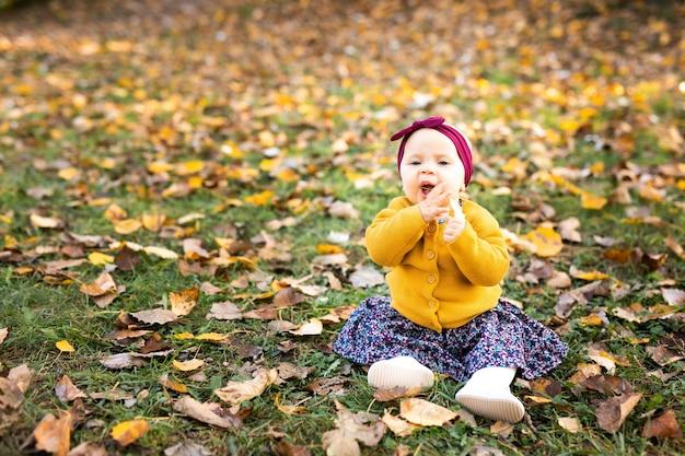 Petite fille en veste yelloy et bandeau rouge assis sur l'herbe, jouant dans les feuilles d'automne.