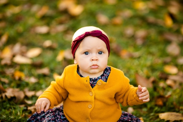 Petite fille en veste yelloy et bandeau rouge assis sur l'herbe