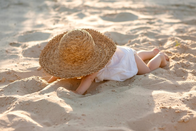 Petite fille en vêtements blancs et un chapeau de paille est assis sur le sable blanc sur la plage en été