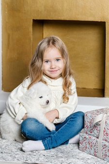 Petite fille en vêtements blancs est assise sur le sol près de l'arbre avec chiot samoyède blanc et souriant.
