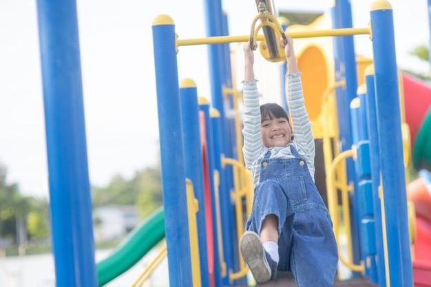 Une petite fille en vêtements décontractés jouant sur une aire de jeux pour enfants, tenant et grimpant. mise au point sélective sur la tête de la fille.