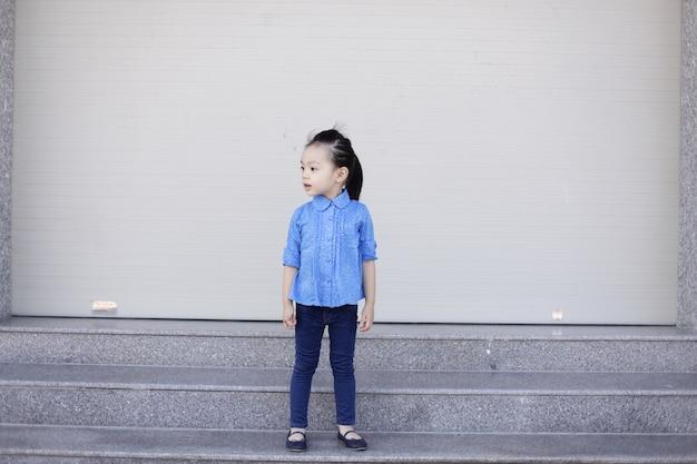 Petite fille avec des vêtements en denim