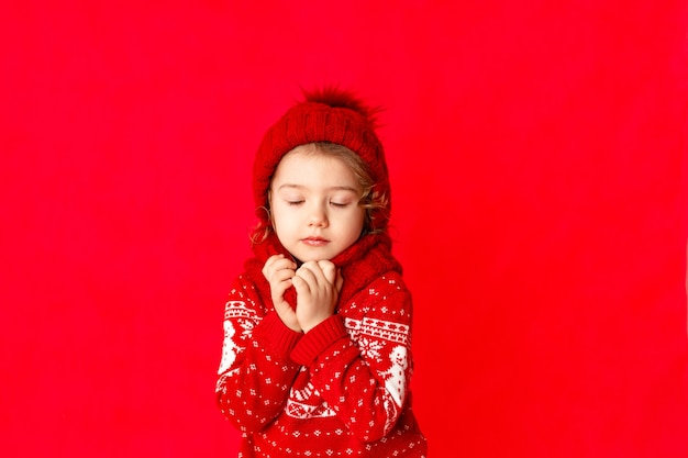 Une petite fille en vêtements d'hiver fait un vœu les yeux fermés sur fond rouge. concept du nouvel an, place pour le texte