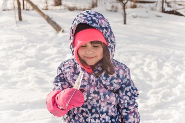 Petite fille en vêtements d'hiver goûte la glace