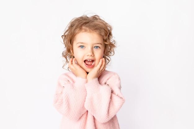 Petite fille en vêtements d'hiver rose sur fond blanc se réjouit, espace pour le texte