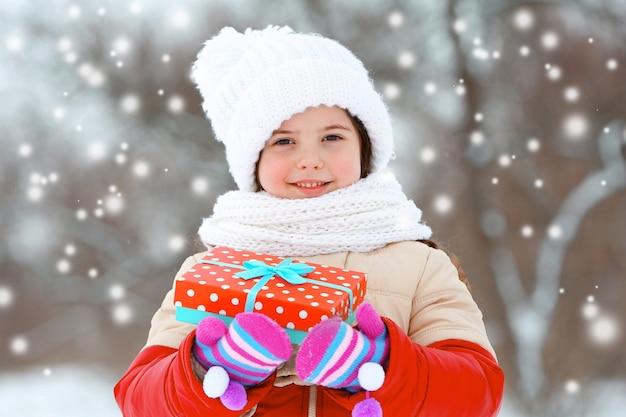Petite fille avec des vêtements d'hiver tenant une boîte-cadeau de noël dans un parc en plein air