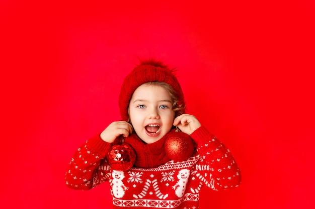 Une petite fille en vêtements d'hiver tient des boules de noël comme boucles d'oreilles sur fond rouge. concept du nouvel an, espace pour le texte