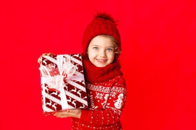 Une petite fille en vêtements d'hiver tient un cadeau sur fond rouge. concept du nouvel an, espace pour le texte