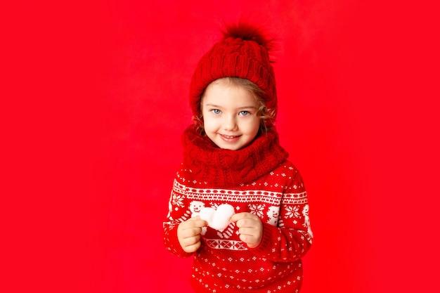 Une petite fille en vêtements d'hiver tient un cœur sur fond rouge. concept du nouvel an ou de la saint-valentin, place pour le texte