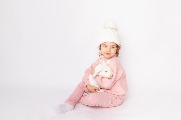 Une petite fille en vêtements d'hiver tient un lapin sur fond blanc. concept du nouvel an, espace pour le texte