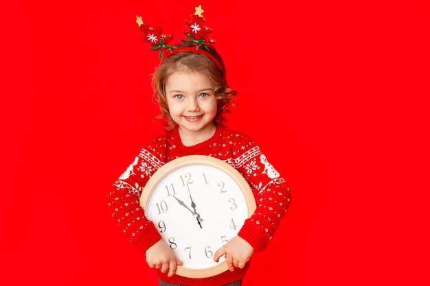 Une petite fille en vêtements d'hiver tient une montre sur fond rouge. concept du nouvel an, espace pour le texte