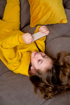 Petite fille en vêtements jaunes est allongée sur le dos sur le lit et tient un smartphone dans ses mains