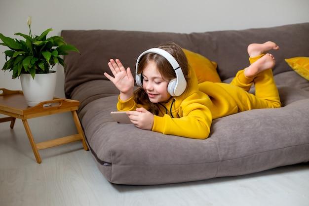 Petite fille en vêtements jaunes est allongée sur le lit et communique sur les réseaux sociaux via un smartphone