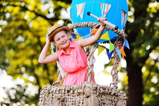 Une petite fille en vêtements roses avec un chapeau de paille et un télescope dans ses mains sourit dans le panier d'un ballon bleu.
