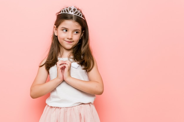 Petite fille vêtue d'un look princesse, établissant un plan à l'esprit, mettant en place une idée.
