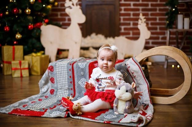 Une petite fille vêtue d'un pull chaud se tient avec un arbre de noël avec des jouets et des cadeaux. ambiance festive du nouvel an de l'enfance heureuse